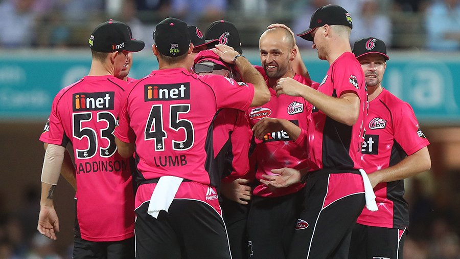 Nathan Lyon is mobbed by team-mates after taking a wicket
